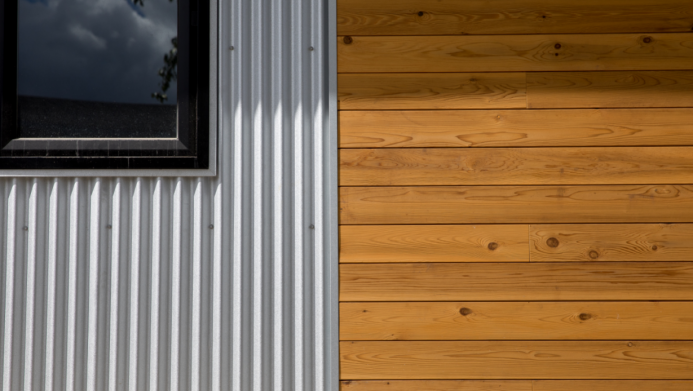 Exterior home comparison of metal sheeting and stained wood.